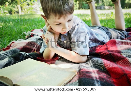 little boy reading a book while lying on a mat in the park. close-up, horizontal #419695009