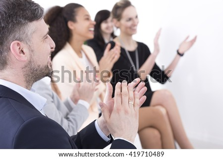 Shot of a team of businesspeople clapping hands while having a meeting  #419710489