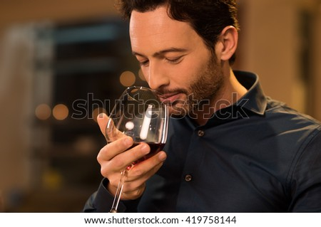 Handsome young man smelling red wine before drinking it. Young man drinking red wine in a luxury restaurant. Handsome young man tasting a glass of red wine during dinner. #419758144