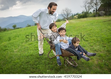 Father playing with sons using trolley on meadow #419770324