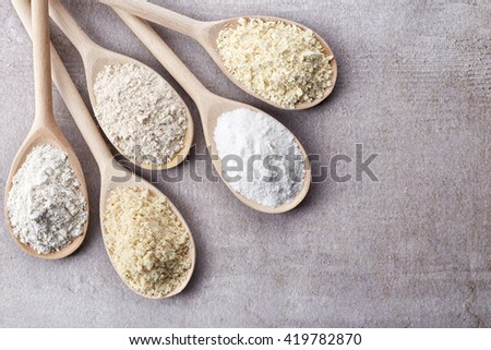 Wooden spoons of various gluten free flour (almond flour, amaranth seeds flour, buckwheat flour, rice flour, chick peas flour) from top view #419782870