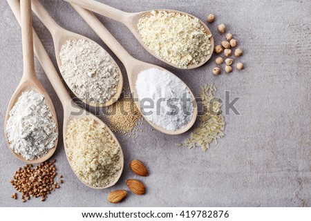 Wooden spoons of various gluten free flour (almond flour, amaranth seeds flour, buckwheat flour, rice flour, chick peas flour) from top view Royalty-Free Stock Photo #419782876