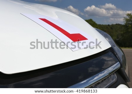 magnetic British L-plate affixed to the front of a white car