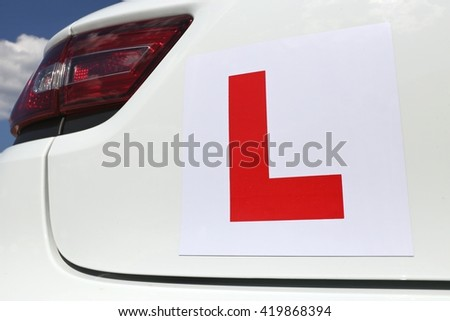 magnetic British L-plate affixed to the back of a white car