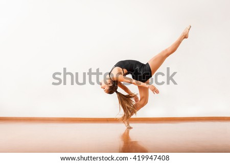 Profile view of a beautiful and flexible young woman showing some of her moves in the dance floor #419947408