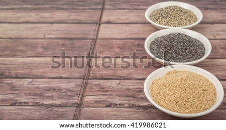 White poppy seed, black poppy seed and mix poppy seed in white bowls over wooden background #419986021
