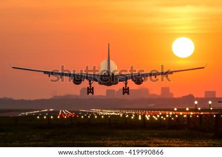 Passenger plane is landing during a wonderful sunrise. Royalty-Free Stock Photo #419990866