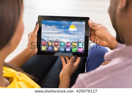 Close-up Of Couple Using Digital Tablet With Multicolored Apps On It #420078127