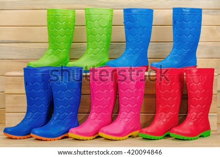 colorful rain boots on a wood background. #420094846