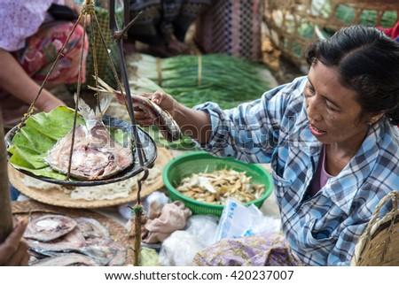 Woman selling fish on Inle lake floating market. Inle lake, Myanmar - 27/MAR/2015 #420237007