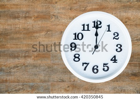 The round white clock shows the time of 12 am or pm. The clock is background is brown wooden with copy space. clipping path in a picture.