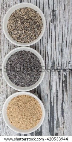 White poppy seed, black poppy seed and mix poppy seed in white bowls over wooden background #420533944