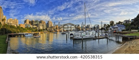 Lavender bay of Sydney Harbour with marina yacht club and docked boats in front of city CBD skyscrapers and Harbour Bridge. Royalty-Free Stock Photo #420538315