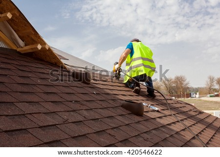 Construction worker putting the asphalt roofing (shingles) with nail gun on a large commercial apartment building development #420546622