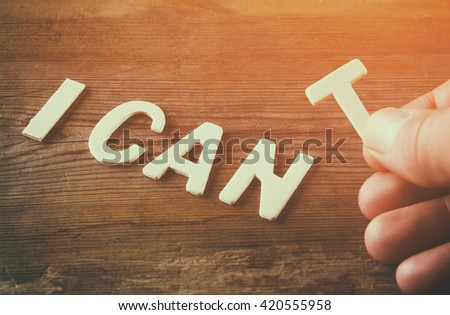 man hand spelling the word I CAN'T from wooden letters, cutting the letter T so it written I CAN. success and challenge concept. retro style image  Royalty-Free Stock Photo #420555958