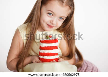Little girl celebrating a birthday with a  small red velvet cake. Cute blond preschooler holding beautiful tasty cake with strawberry #420562978