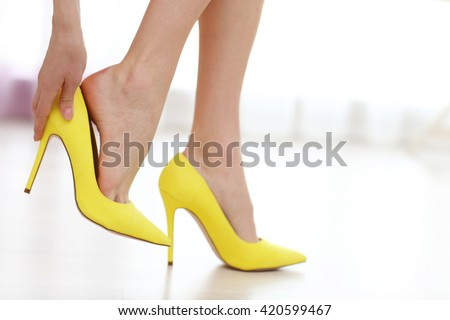 Woman taking off yellow high heels shoes. Royalty-Free Stock Photo #420599467