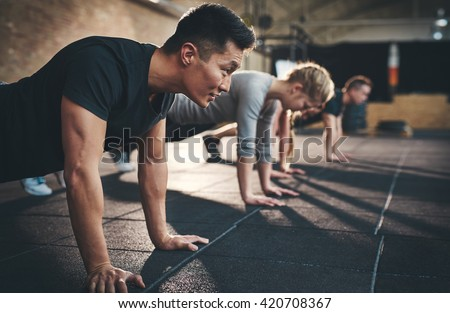 Fit young people doing pushups in a gym looking focused #420708367