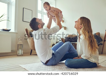 Proud father holding his newborn baby daughter in the air, with smiling mother sitting on the floor at home #420716029