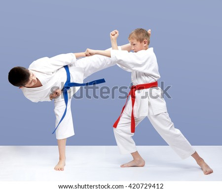 On a light background boys are beating punch arm and kick leg #420729412