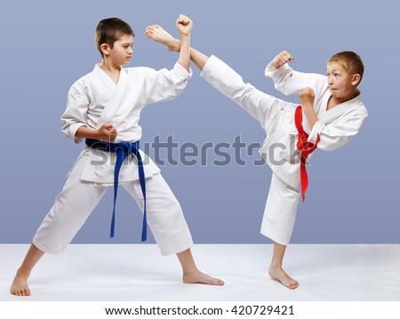 Kick leg and block are doing sportsmen in karategi #420729421
