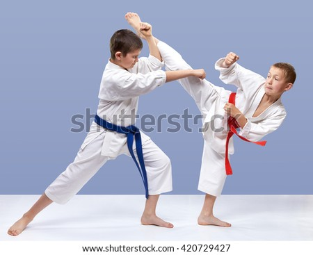 The boys are training strikes and blocks on a light background #420729427