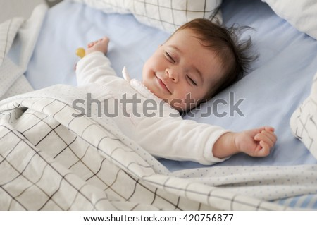 Smiling baby girl lying on a bed sleeping on blue sheets Royalty-Free Stock Photo #420756877