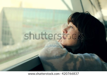 Portrait of beautiful 40 years old woman standing near the window #420766837