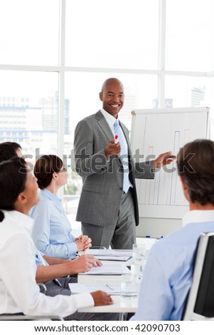 Afro-American businessman introducing stock market to his team in the office #42090703