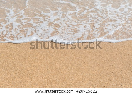 Wave of the sea on the sandy beach background #420915622