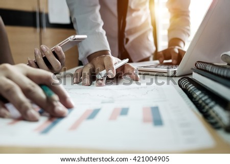 business documents on office table with smart phone and laptop and two colleagues discussing data in the background in morning light #421004905