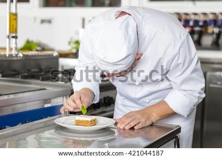 Professional chef decorate dessert cake with lemon leaf #421044187