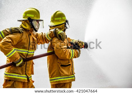 Fireman  attacking a fire with water. firefighter team work. Royalty-Free Stock Photo #421047664
