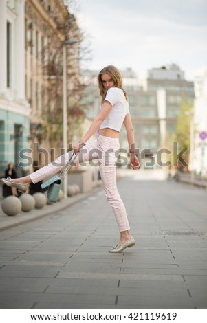 young blonde girl walks through the streets of the city. center of Moscow. Summer hot sunny day. girl dressed in pink pants and white topic #421119619