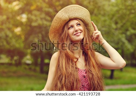 portrait of a beautiful smiling woman in a hat in a summer park #421193728