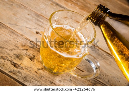 Pouring cold lager from a large bottle #421264696