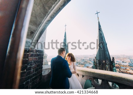 Gentle beautiful bride and groom holding hands embracing face-to-face on the ancient balcony, background cityscape  #421334668