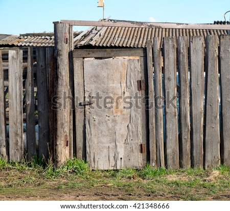 Old wooden fence and a door in the countryside #421348666