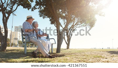 Full length outdoor shot of senior couple sitting on a bench on a summer day. Retired man and woman relaxing outdoors. #421367551