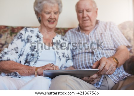 Portrait of happy senior couple sitting together at home and using digital tablet. Elderly man and woman sitting on sofa using touchscreen computer. #421367566