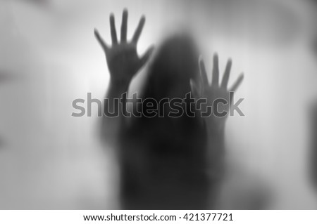 Horror woman behind the matte glass in black and white. Blurry hand and body figure abstraction. Royalty-Free Stock Photo #421377721