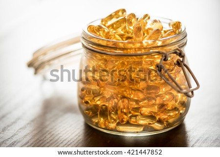 Omega 3-6-9 fish oil yellow softgels on wooden black board into airtight glass jar #421447852