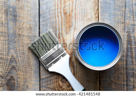 painting at home with can blue paint on wooden background #421481548