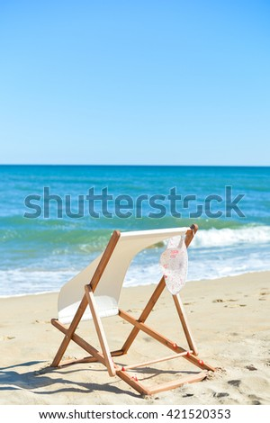 Female hat and deckchair on the beach vacation, sunny outdoors background #421520353