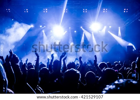 silhouettes of concert crowd in front of bright stage lights #421529107