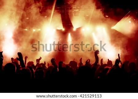 silhouettes of concert crowd in front of bright stage lights #421529113