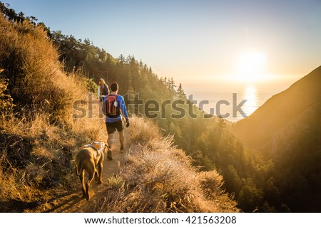 Man, woman, and dog hike in Big Sur, CA as the sun sets over the ocean. Royalty-Free Stock Photo #421563208