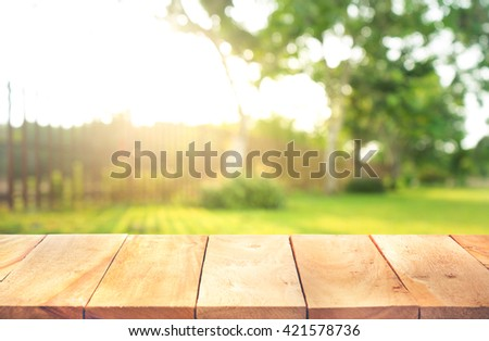 Wood table top with fence and grass in garden background.For  create product display or design key visual layout #421578736