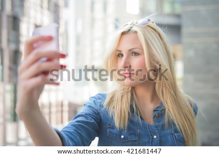 Half length of a young beautiful blonde caucasian girl using a smart phone taking a selfie - communication, technology, social network concept #421681447