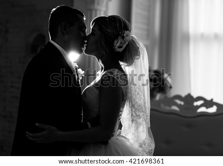 Silhouette of a bride and groom kissing #421698361